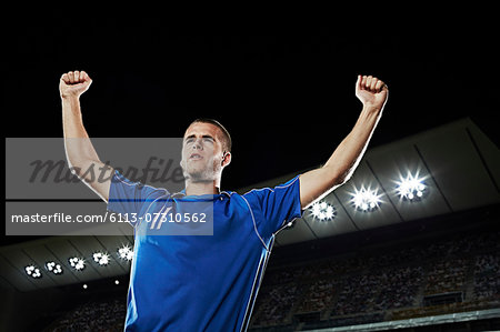 Soccer player cheering in stadium Stock Photo - Premium Royalty-Free, Image code: 6113-07310562