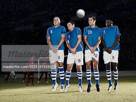 Soccer players jumping on field Stock Photo - Premium Royalty-Free, Image code: 6113-07310570