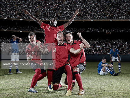 Soccer players cheering on field Stock Photo - Premium Royalty-Free, Image code: 6113-07310573