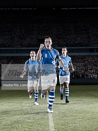 Soccer players running on field Stock Photo - Premium Royalty-Free, Image code: 6113-07310574