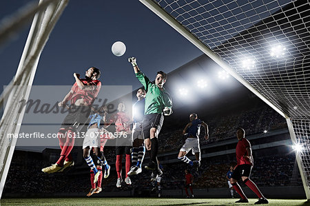 Soccer players defending goal Stock Photo - Premium Royalty-Free, Image code: 6113-07310576