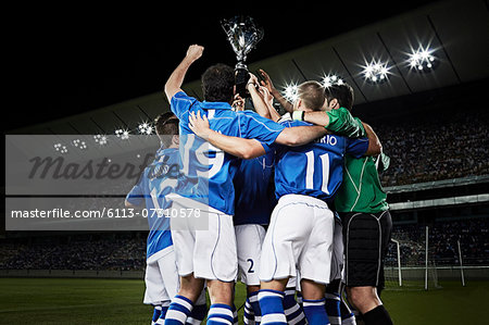 Soccer team cheering with trophy on field Stock Photo - Premium Royalty-Free, Image code: 6113-07310578