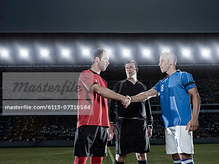 Soccer players shaking hands on field Stock Photo - Premium Royalty-Free, Image code: 6113-07310584