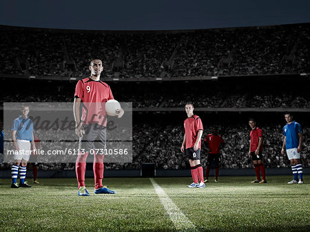 Soccer player holding ball on field Stock Photo - Premium Royalty-Free, Image code: 6113-07310586