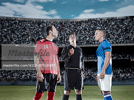 Referee tossing coin in soccer game Stock Photo - Premium Royalty-Free, Image code: 6113-07310587
