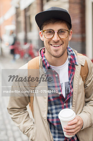 Man with cup of coffee on city street Stock Photo - Premium Royalty-Free, Image code: 6113-07542440