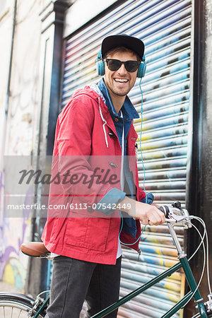 Man pushing bicycle on city street