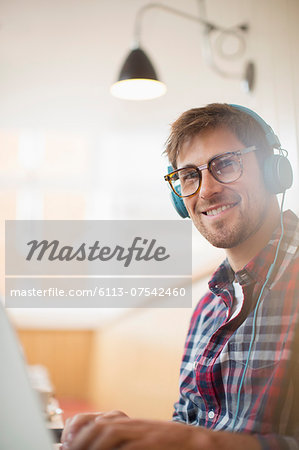 Man wearing headphones and using laptop Stock Photo - Premium Royalty-Free, Image code: 6113-07542460