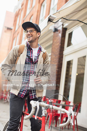 Man drinking coffee on bicycle on city street
