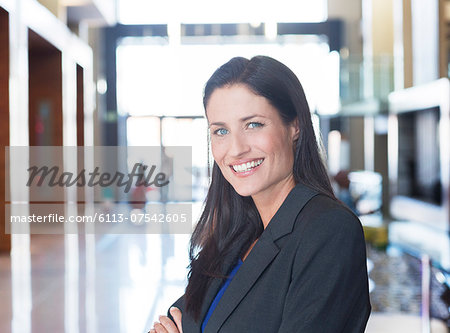 Businesswoman smiling in lobby Stock Photo - Premium Royalty-Free, Image code: 6113-07542605