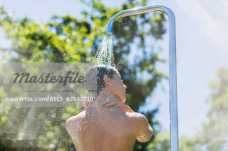Woman showering outdoors Stock Photo - Premium Royalty-Free, Image code: 6113-07542710