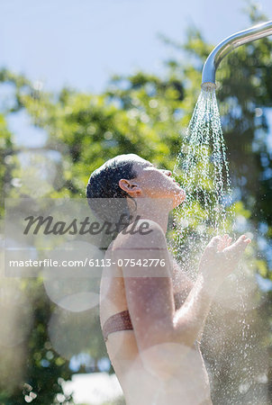 Woman showering outdoors Stock Photo - Premium Royalty-Free, Image code: 6113-07542776