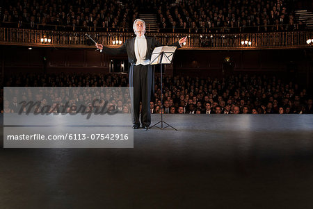 Conductor performing on stage in theater Stock Photo - Premium Royalty-Free, Image code: 6113-07542916