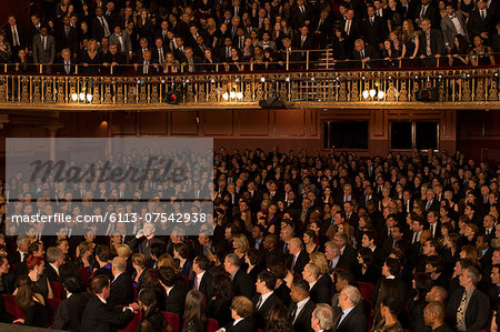 Spotlight on audience member using cell phone in theater Stock Photo - Premium Royalty-Free, Image code: 6113-07542938