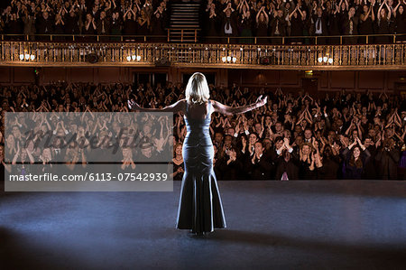 Performer standing with arms outstretched on stage in theater Stock Photo - Premium Royalty-Free, Image code: 6113-07542939