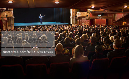 Audience watching performer on stage in theater Stock Photo - Premium Royalty-Free, Image code: 6113-07542955