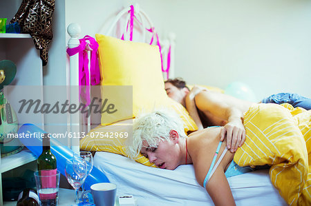 Couple sleeping in bed the morning after a party Stock Photo - Premium Royalty-Free, Image code: 6113-07542969