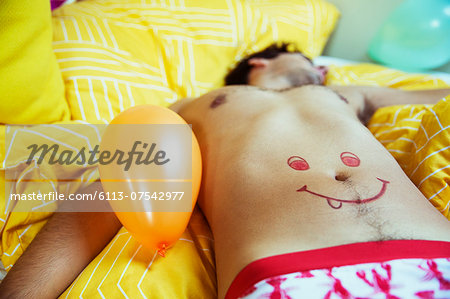 Man with smiley face drawing on belly sleeping after party Stock Photo - Premium Royalty-Free, Image code: 6113-07542977