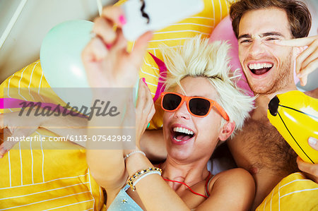 Couple taking self-portraits in bed at party Stock Photo - Premium Royalty-Free, Image code: 6113-07542992
