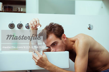 Hungover man watching effervescent tablets in bathroom Stock Photo - Premium Royalty-Free, Image code: 6113-07543010