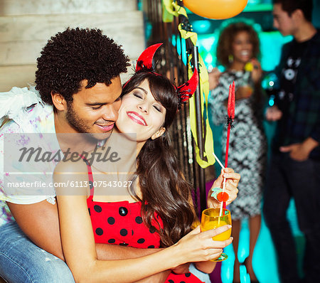 Man hugging girlfriend at party Stock Photo - Premium Royalty-Free, Image code: 6113-07543027