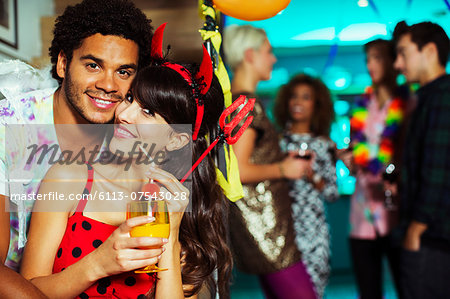 Man hugging girlfriend at party Stock Photo - Premium Royalty-Free, Image code: 6113-07543028
