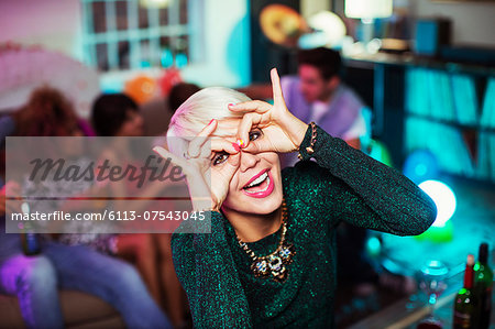 Woman making face in living room at party Stock Photo - Premium Royalty-Free, Image code: 6113-07543045