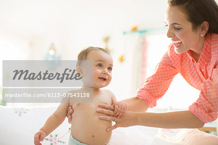 Mother helping baby boy walk Stock Photo - Premium Royalty-Free, Image code: 6113-07543138