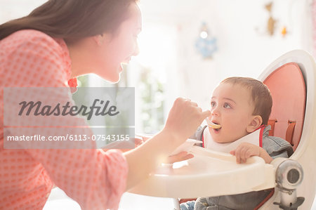 Mother feeding baby boy in high chair Stock Photo - Premium Royalty-Free, Image code: 6113-07543155