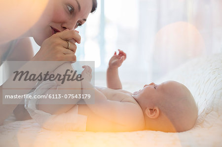 Mother kissing baby girl's feet Stock Photo - Premium Royalty-Free, Image code: 6113-07543179