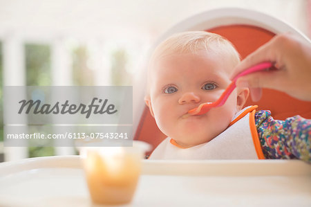 Mother feeding baby girl in high chair Stock Photo - Premium Royalty-Free, Image code: 6113-07543241