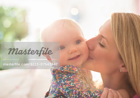 Mother kissing baby girl's cheek Stock Photo - Premium Royalty-Free, Image code: 6113-07543247