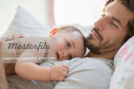 Father laying with baby boy on bed Stock Photo - Premium Royalty-Free, Image code: 6113-07543250