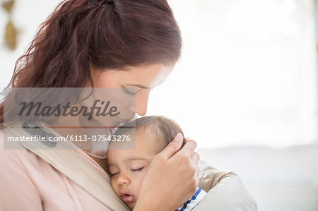Mother kissing sleeping baby girl Stock Photo - Premium Royalty-Free, Image code: 6113-07543276