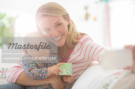 Mother taking self-portrait with baby girl Stock Photo - Premium Royalty-Free, Image code: 6113-07543283
