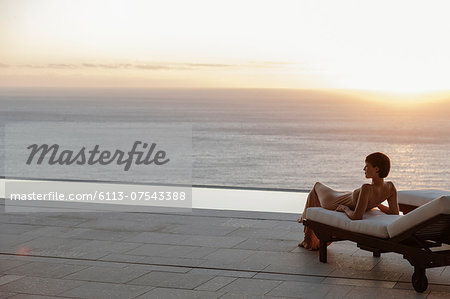 Woman in dress laying on lounge chair on patio overlooking ocean at sunset Stock Photo - Premium Royalty-Free, Image code: 6113-07543388