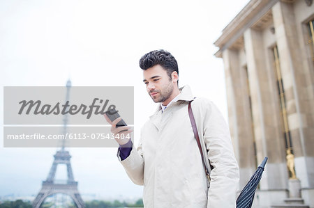 Businessman using cell phone by Eiffel Tower, Paris, France Stock Photo - Premium Royalty-Free, Image code: 6113-07543404