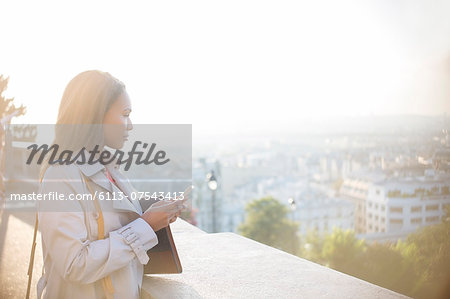 Businesswoman with cell phone overlooking Paris, France Stock Photo - Premium Royalty-Free, Image code: 6113-07543413