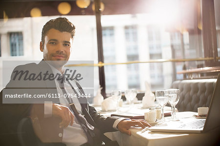 Businessman smiling in restaurant Stock Photo - Premium Royalty-Free, Image code: 6113-07543444