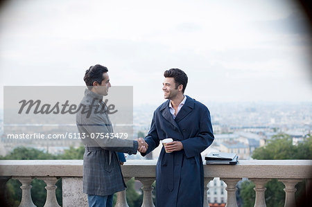 Businessmen shaking hands at railing overlooking Paris, France Stock Photo - Premium Royalty-Free, Image code: 6113-07543479