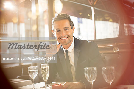 Businessman smiling at restaurant Stock Photo - Premium Royalty-Free, Image code: 6113-07543493