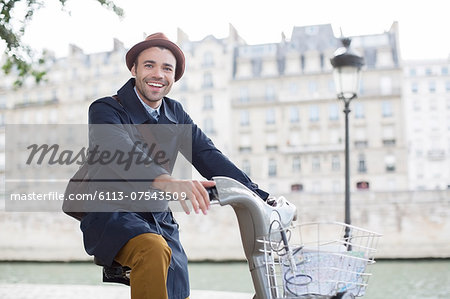 Businessman on bicycle along Seine River, Paris, France