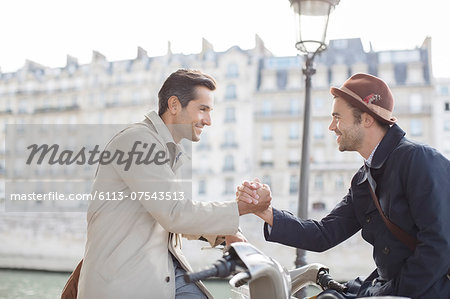 Businessmen shaking hands on bicycles along Seine River, Paris, France