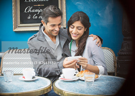 Couple using cell phone at sidewalk cafe, Paris, France Stock Photo - Premium Royalty-Free, Image code: 6113-07543532