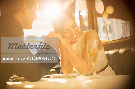 Couple holding hands in restaurant Stock Photo - Premium Royalty-Free, Image code: 6113-07543540