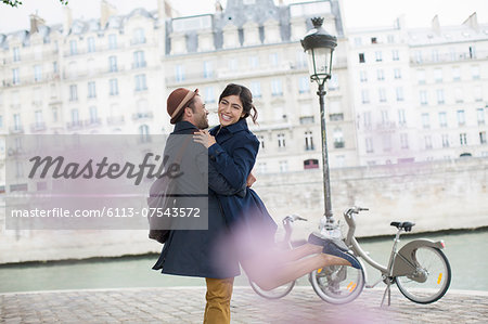 Couple hugging along Seine River, Paris, France Stock Photo - Premium Royalty-Free, Image code: 6113-07543572