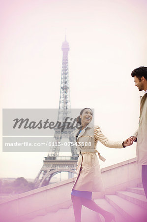 Couple descending stairs by Eiffel Tower, Paris, France Stock Photo - Premium Royalty-Free, Image code: 6113-07543588