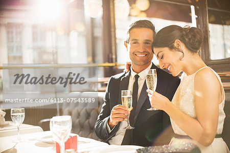 Well-dressed couple drinking champagne in restaurant Stock Photo - Premium Royalty-Free, Image code: 6113-07543589