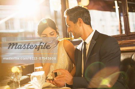 Man proposing to girlfriend in restaurant Stock Photo - Premium Royalty-Free, Image code: 6113-07543606
