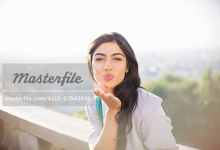 Woman blowing a kiss outdoors Stock Photo - Premium Royalty-Free, Image code: 6113-07543616